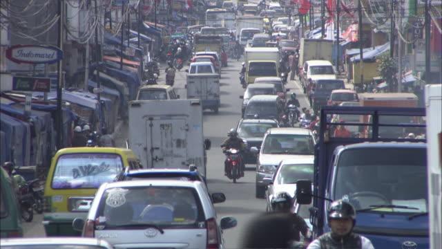medium shot tilt down - busy traffic filled street / indonesia - indonesia street stock videos & royalty-free footage