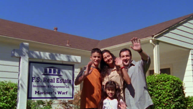 medium shot tilt down family waving next to real estate sign with house in background / california - waving stock videos & royalty-free footage