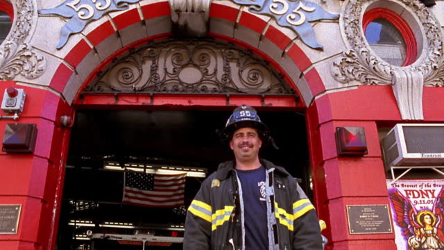 Medium shot tilt down firefighter posing in front of firehouse / NYC