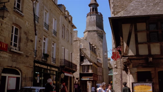Medium shot tilt down from church tower to people walking on town street / Dinan