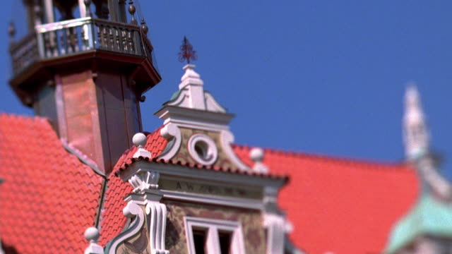 Medium shot tilt down from onion dome and spire to building covered in intricate paintings / Prague, Czech Republic