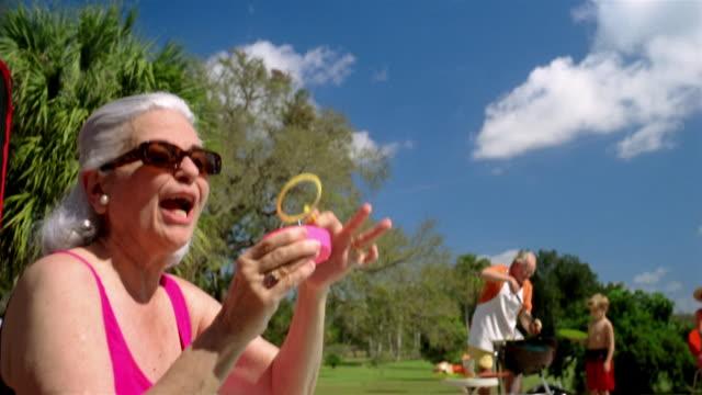 vídeos y material grabado en eventos de stock de medium shot tilt down grandmother blowing bubbles / grandfather and grandson barbecuing in background - traje de baño