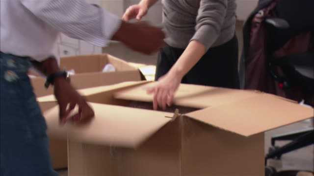 Medium shot tilt down man and woman unpacking box in new office space/ tilt up man and woman looking at object/ Brooklyn, New York