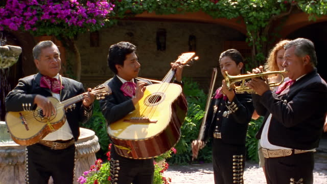 Medium shot tilt down mariachi band performing in courtyard / man taking woman's picture with band
