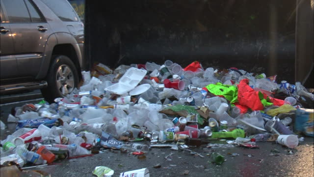medium shot tilt down pan left - truck sweeping large pile of trash along street, mostly plastic cups / new orleans louisiana - plastic stock videos & royalty-free footage