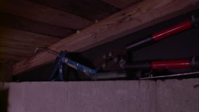 Medium Shot Tilt Down - Tilt down from basement ceiling to shelves with miscellaneous supplies /