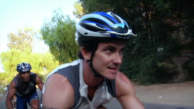Medium shot tilt down tilt down man riding bike leading pack of other cyclists / pan to man behind him