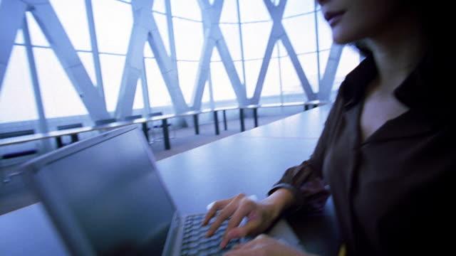vídeos de stock, filmes e b-roll de medium shot tilt down tilt up asian businesswoman typing on laptop computer in large sunlit room - trabalhadora de colarinho branco