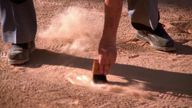 medium shot tilt down tilt up baseball umpire sweeping dirt off home plate with brush - referee stock videos & royalty-free footage