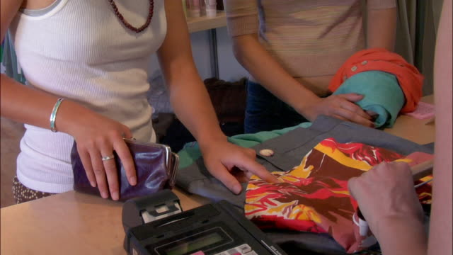 medium shot tilt down tilt up saleswoman ringing up purchases for two young women in clothing store - strategia di vendita video stock e b–roll