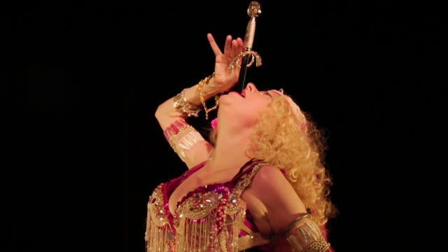 medium shot tilt down woman swallowing sword - sword stock videos & royalty-free footage