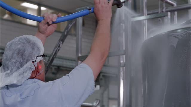 Medium shot tilt down worker spraying water to rinse off tank at a water purification plant / San Antonio, Texas