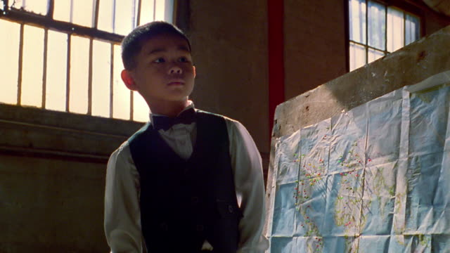 Medium shot tilt up Asian boy in bow tie standing next to world map and putting tack on it / Nova Scotia, Canada
