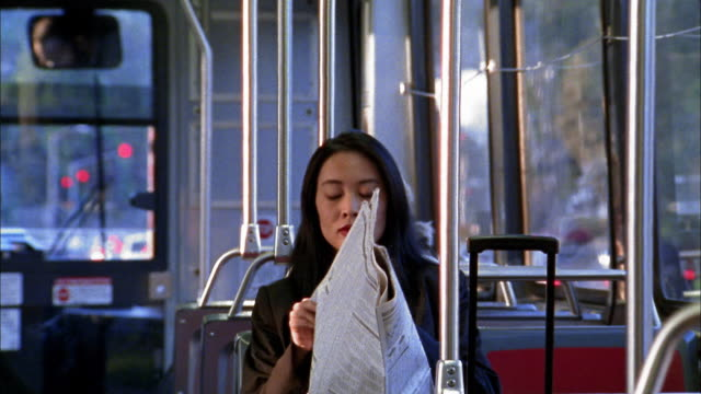 Medium shot tilt up Asian businesswoman reading financial section of ewspaper on train or bus