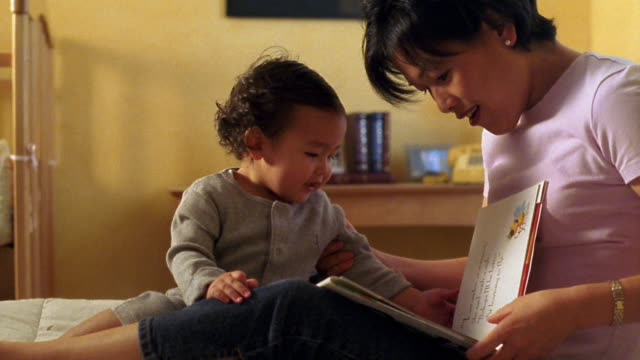 Medium shot tilt up Asian woman reading story book to toddler on bed with toddler turning pages and laughing