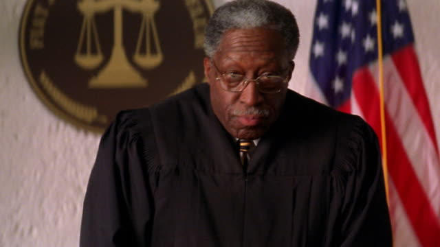 medium shot tilt up black senior judge standing up and pointing / american flag in background - court room stock videos & royalty-free footage