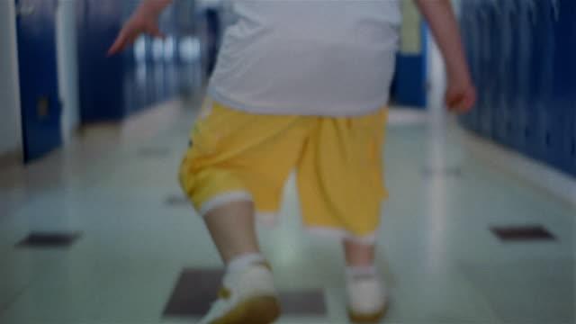 Medium shot tilt up boy cutting class walking down empty hallway of school / sneaking past classrooms