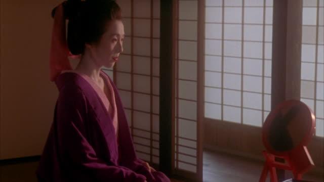 medium shot tilt up courtesan wearing kimono standing up and leaving room / hagi, yamaguchi prefecture, japan - kimono stock videos and b-roll footage