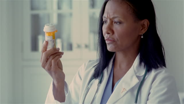 stockvideo's en b-roll-footage met medium shot tilt up doctor looking at prescription bottle/ solebury, pennsylvania - alleen oudere vrouwen