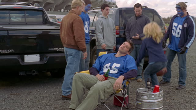 medium shot tilt up drunk man asleep in chair at tailgate party as people stand behind him/ connecticut - アメフトのユニフォーム点の映像素材/bロール
