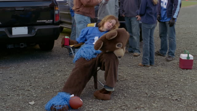 Medium shot tilt up drunk woman in bear mascot costume at tailgate party as people stand behind her/ Connecticut