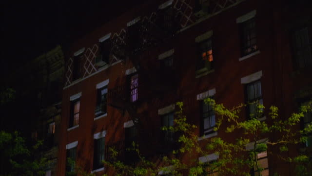 vídeos de stock, filmes e b-roll de medium shot tilt up exterior of an apartment building at night / person raising shade in window / new york city - persiana
