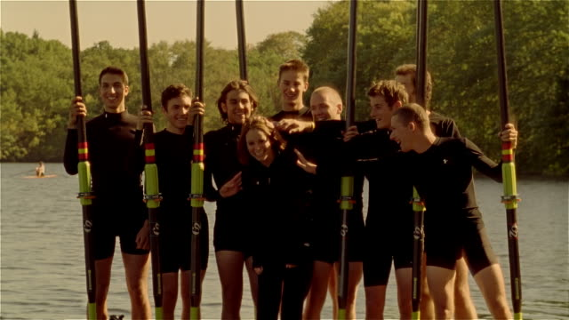 medium shot tilt up from water to portrait of crew team standing on pier holding oars / posing with coxswain / tousling her hair - einzelne frau mit männergruppe stock-videos und b-roll-filmmaterial