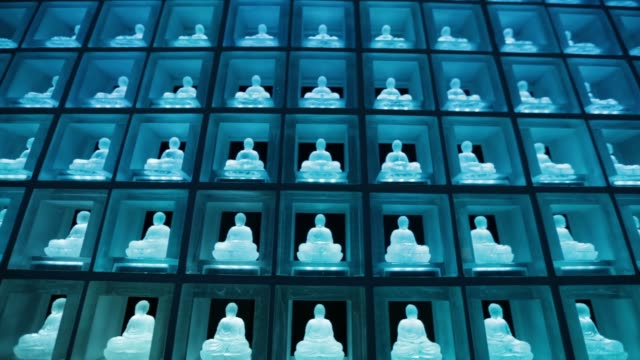 medium shot tilt up glass buddha statues illuminated by lightemitting diodes sit inside the ruriden columbarium at the koukokuji temple in tokyo... - buddha stock videos & royalty-free footage