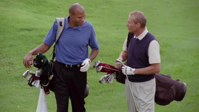 medium shot tilt up golfing men carrying bags on green and talking/ phoenix, arizona - only mature men stock videos & royalty-free footage