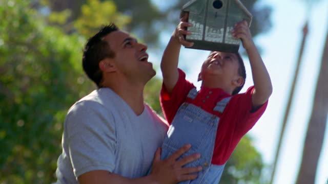 Medium shot tilt up Hispanic man lifting young boy to hang birdhouse on tree branch / Arizona