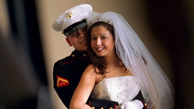 Medium shot tilt up Hispanic U.S Marine groom hugging Hispanic bride from behind / bride and groom laughing