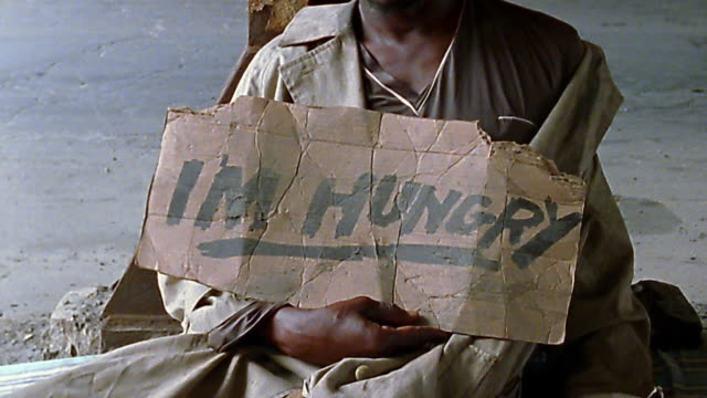 "medium shot tilt up homeless black man holding ""i'm hungry"" sign - hungrig stock-videos und b-roll-filmmaterial"