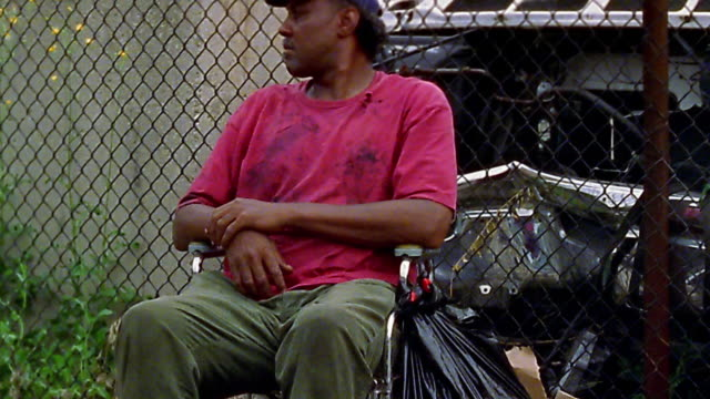 medium shot tilt up homeless black man in wheelchair - disability stock videos & royalty-free footage