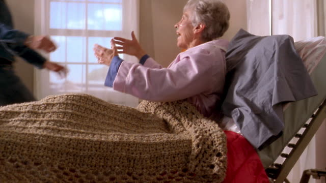 Medium shot tilt up ill elderly woman lying in bed w/blanket /  hugging young woman sitting on edge of bed