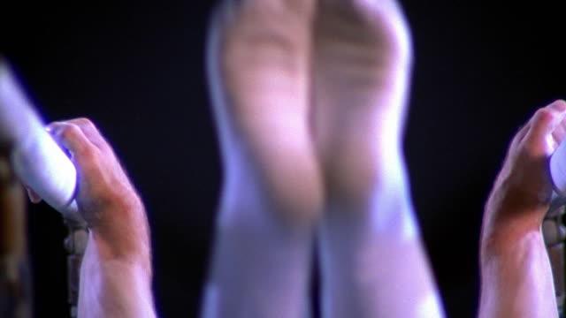 medium shot tilt up male gymnast mounting parallel bars and doing routine - barr bildbanksvideor och videomaterial från bakom kulisserna