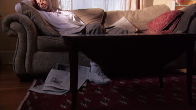 vídeos y material grabado en eventos de stock de medium shot tilt up man asleep on sofa with newspapers and remote control in lap - mesa baja de salón