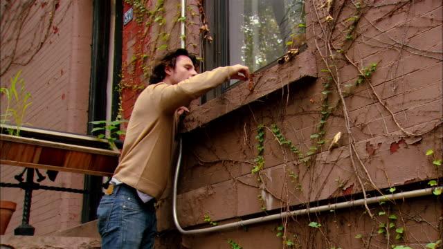 vídeos de stock e filmes b-roll de medium shot tilt up man on ladder working on window/ woman bringing man cup of coffee/ brooklyn, new york - gola alta