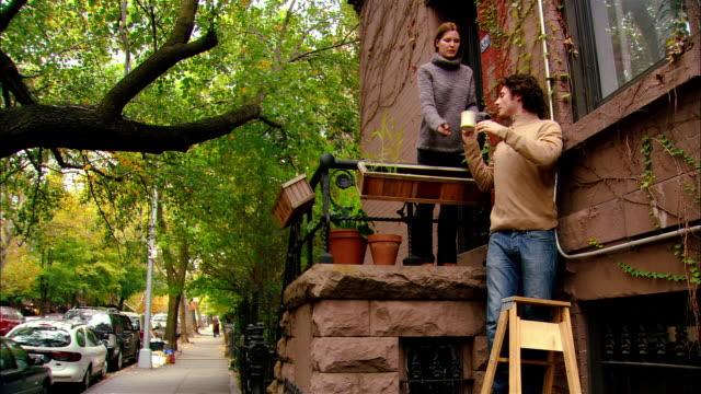 vídeos de stock e filmes b-roll de medium shot tilt up man on ladder working on window/ woman bringing man cup of coffee/ woman waving/ brooklyn, new york - gola alta