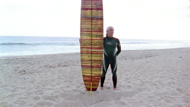 Medium shot tilt up man standing on beach next to surfboard with surf in background / picking up board and walking