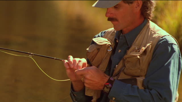 Medium shot tilt up man tying line while fly fishing / Arizona