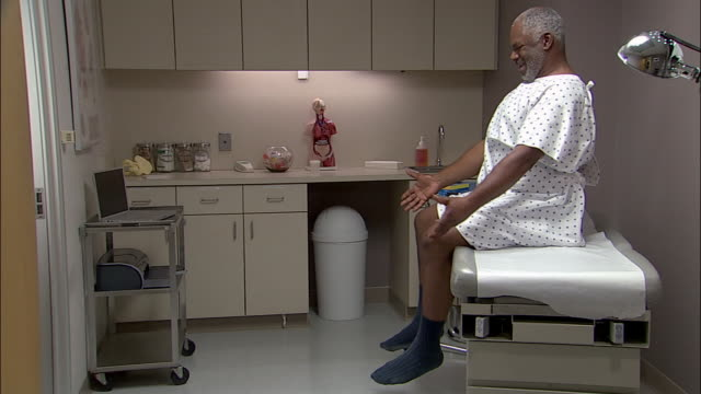 Medium shot tilt up man wearing hospital gown sitting on exam table in doctor's office