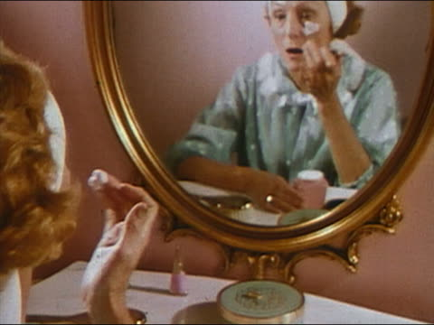 vidéos et rushes de 1966 medium shot tilt up middle-aged woman dabbing cream on face / audio - prelinger archive