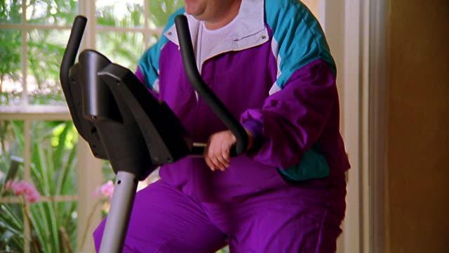 vídeos de stock e filmes b-roll de medium shot tilt up overweight man in warmup suit pedaling on stationary exercise bike - só um homem maduro