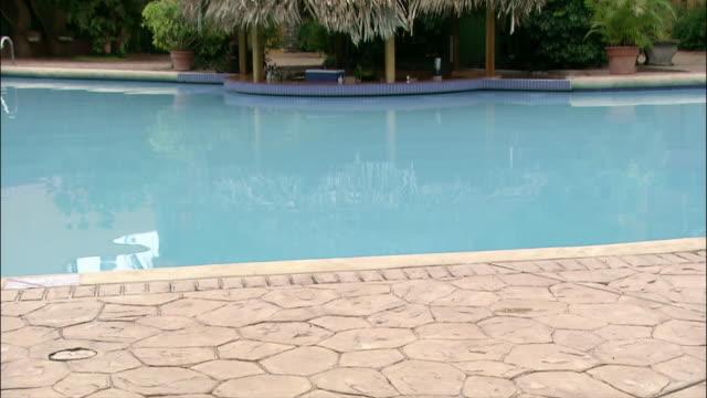 medium shot tilt up pool and gazebo at resort/ san jose, costa rica - プールサイド点の映像素材/bロール
