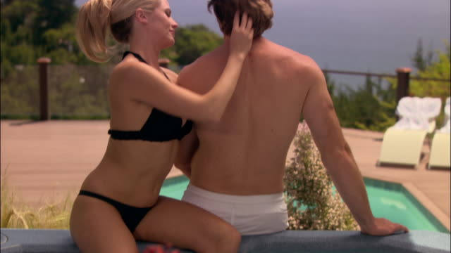 medium shot tilt up portrait man and woman hugging in hot tub at spa/ monterey county, california - ragged point stock videos and b-roll footage