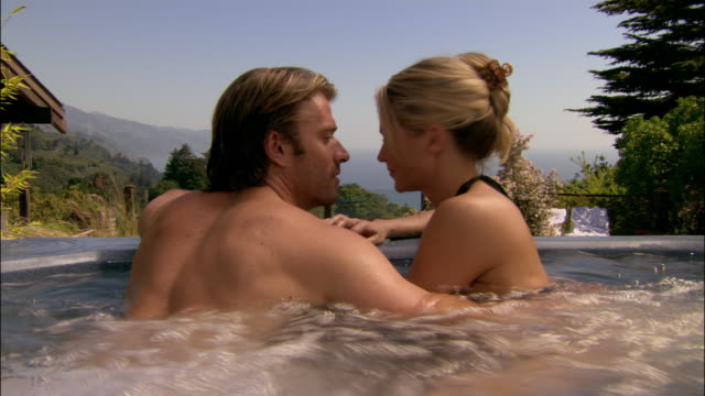 Medium shot tilt up portrait man and woman in hot tub, looking at view of ocean/ man and woman kissing/ Monterey County, California