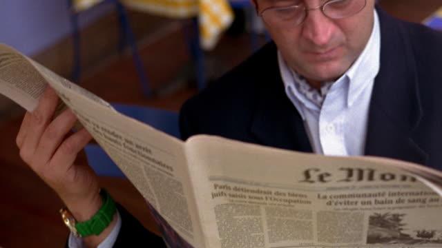 vidéos et rushes de medium shot tilt up portrait pan middle age man reading newspaper in cafe looks at camera then hides face / cannes - journal