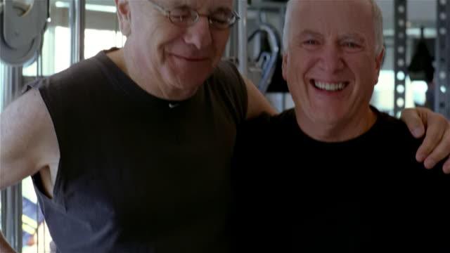 medium shot tilt up portrait two senior men at gym/ solebury, pennsylvania - arm around stock videos & royalty-free footage