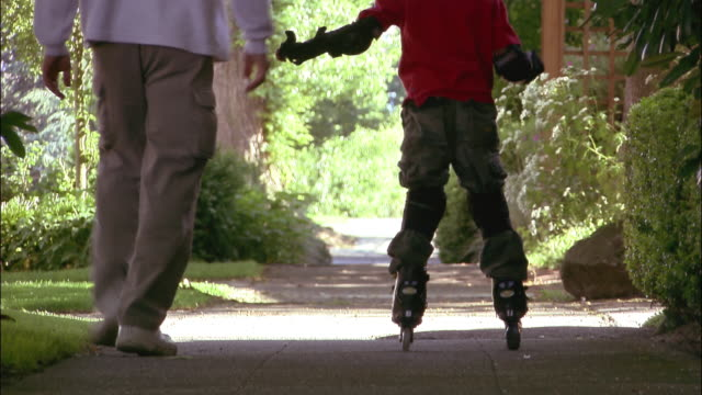 medium shot tilt up rear view of father running alongside son wearing roller blades - elbow pad stock videos & royalty-free footage
