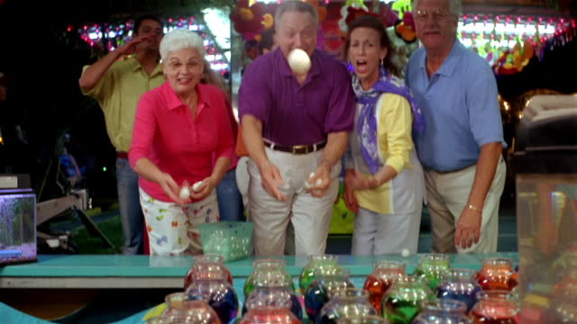 Medium shot tilt up senior couples playing game at amusement park